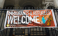 A sign hanging on the fence of the Church of St. Francis Xavier in the Chelsea neighborhood of New York on Saturday, June 17, 2017 welcomes immigrant and refugees. (© Richard B. Levine)