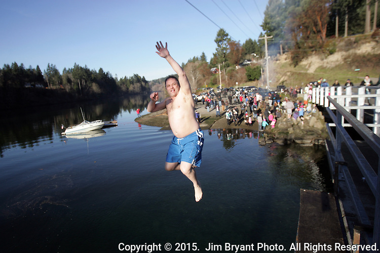 A leaper hurls off the bridge into the Burley Lagoon during the 31st annual Polar Bear on January 1, 2015 in Olalla, Washington. Over 500 hardy participants joined in on the annual New Year's Day Tradition by jumping into the chilly lagoon waters during the annual Polar Bear Plunge.  ©2015.  Jim Bryant Photo. All Rights Reserved.