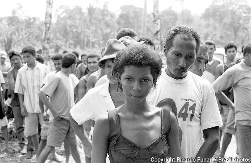 Contemporary slavery, Amazon rainforest, Tuerê Farm, State: Pará, Brazil. Special Group for the Repression of Forced Labour (Groupo Especial de Repressão ao Trabalho Forçado) or GERTRAF, as it is commonly known, is made up of 4 mobile groups that work in different regions of the country, investigating accusations of work conditions close to slavery on farms, charcoal works, plantations and sugar mills.  They are officials of the Ministry of Labour and they have support from the Federal Police..Wretched people lined up, waiting to be photographed and having those photographs pasted into the first work permit they had ever had in their lives.  The great majority of those there had left school and had begun their lives of drudgery before the age of 10. Multi-gender group. A woman in the middle of dozens of men.