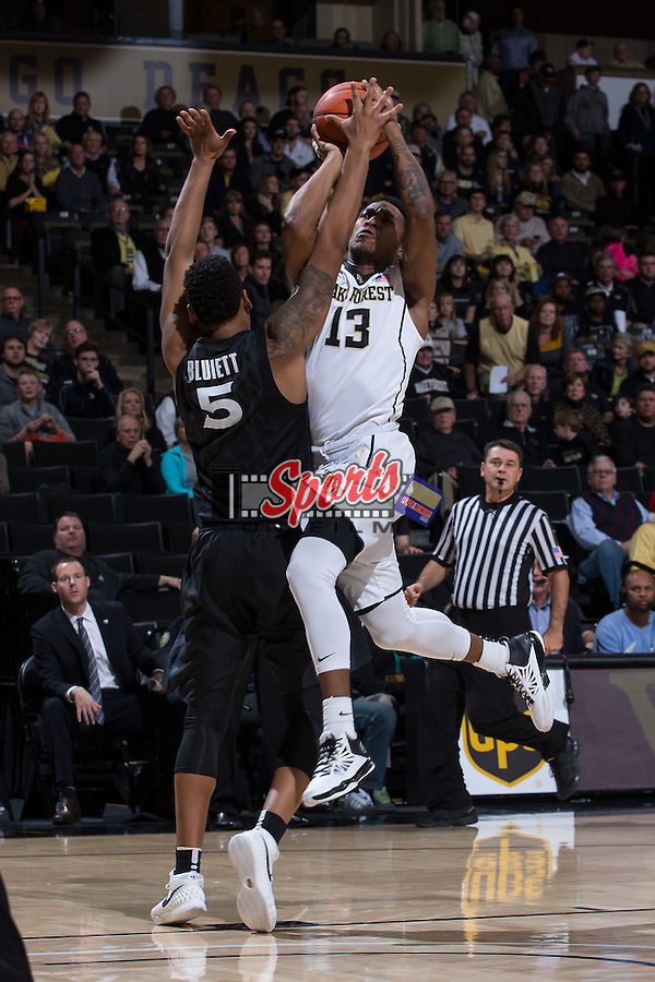 Bryant Crawford (13) of the Wake Forest Demon Deacons draws contact from Trevon Bluiett (5) of the Xavier Musketeers at the LJVM Coliseum on December 22, 2015 in Winston-Salem, North Carolina.  The Musketeers defeated the Demon Deacons 78-70.  (Brian Westerholt/Sports On Film)