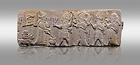 Aslantepe Hittite relief sculpted orthostat stone panel. Limestone, Aslantepe, Malatya, 1200-700 B.C. . Anatolian Civilisations Museum, Ankara, Turkey<br /> <br /> Scene of the king's offering drink and sacrifice to the gods. King pours from the pitcher to the vessel (libation); behind the king is a servant bringing a sacrifice. Storm God across the king holds Teshup, a triple lightning bundle - sickle, and a spear-mace set in the other orthostat; the goddess Ishtar holds weapon in both. All six figures have shoes with the curled ends. <br /> <br /> Against a gray background.