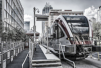This is the Austin Rail in a almost black and white version of the Metro Rail as it leave downtown.  This cityscape show the Convention Center along side the rail and the Frost Tower in the background with the Westin and Courtyard Marriott and is located just a couple blocks from six street. This is a modern image of an contemporary urban environment.