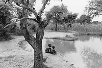 Sudan. Southern part. Bahr El Ghazal. Marial Lou. Dinka tribe area.Two boys seat on the ground and have their feet in the water from a flood due to heavy rains. People suffer mostly  from the guinean worm disease catched by using  (drinking or bathing) in dirty water. A man is seated on a brench in a tree. © 1998 Didier Ruef