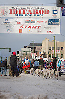 Jim Lanier and team leave the ceremonial start line with an Iditarider at 4th Avenue and D street in downtown Anchorage, Alaska during the 2015 Iditarod race. Photo by Jim Kohl/IditarodPhotos.com