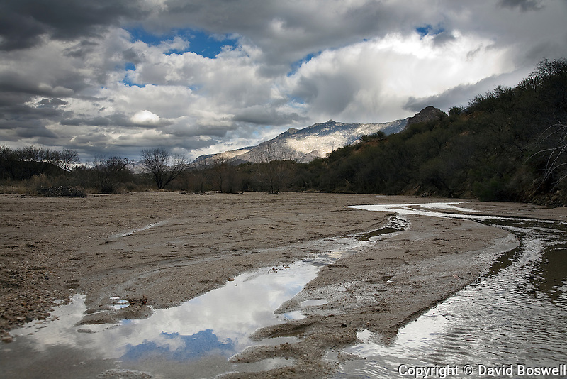 Clouds reflect in a seasonal stream as a storm gathers over Catalina State Park, north of Tucson, Arizona.
