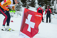 Switzerland. Canton Ticino. Swiss-Cups Campra. Cross Country Skiing. FIS Classic Sprint Race. Hippolyt Kempf  (R) is the Cross Country Skiing Chef by Swiss-Ski. He stands in the snow holding two ski poles and watches the race. Bernhard Aregger (C) is the CEO of Swiss-Ski. Hippolyt Kempf (born 10 December 1965) is a Swiss Nordic combined skier who competed during the late 1980s and early 1990s. He won a complete set of Olympic medals, earning two of them at the 1988 Winter Olympics in Calgary (gold: 15 km individual, silver: 3 x 10 km team) and the third at the 1994 Winter Olympics in Lillehammer (bronze: 3 x 10 km team). Kempf also earned a 3 x 10 km team silver medal at the 1989 FIS Nordic World Ski Championships in Lahti. A German competitor schusses down the mountain. Athletes are trained to achieve endurance, strength, speed, skill and flexibility at different levels of intensity. A swiss flag used by Swiss-Ski as symbol of its belonging to Switzerland. Swiss-Ski is a branch of Swiss Olympic. The Fédération Internationale de Ski (FIS; English: International Ski Federation) is the world's highest governing body for international winter sports. Founded  on 2 February 1924, it is responsible for the Olympic disciplines of cross-country skiing. The FIS is also responsible for setting the international competition rules. 4.01.2020 © 2020 Didier Ruef