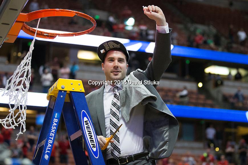 Wisconsin Badgers Direcotor of Basketball Operations Luke Wainwright cuts down a piece of the net after the Western Regional Final NCAA college basketball tournament game against the Arizona Wildcats Saturday, March 29, 2014 in Anaheim, California. The Badgers won 64-63 (OT). (Photo by David Stluka)