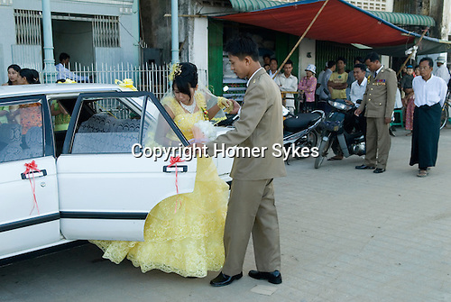 Pathein. ( Bassein )  Young couple arrive at a wedding hall to have their marriage celebrated. Myanmar Burma 2011.