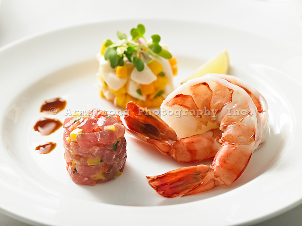 An elegant seafood appetizer plate with prawns and tuna tartar