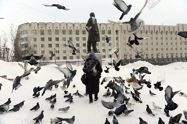 "A woman came to feed pigeons by the statue of Lenin outside the FSB headquarters in Magadan, Russia, a city associated most closely with ""The Gulag Archipeligo."" February 5, 2011"