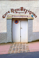 An entrance to a cellar in the village, painted on the wall saying Cave Dom Perignon, owner A Boquet, sale of champagne and a no-parking sign, the village of Hautvillers in Vallee de la Marne, Champagne, Marne, Ardennes, France