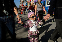 A girl walks with her parents on the Wang Fu Jing pedestrian street in Beijing..