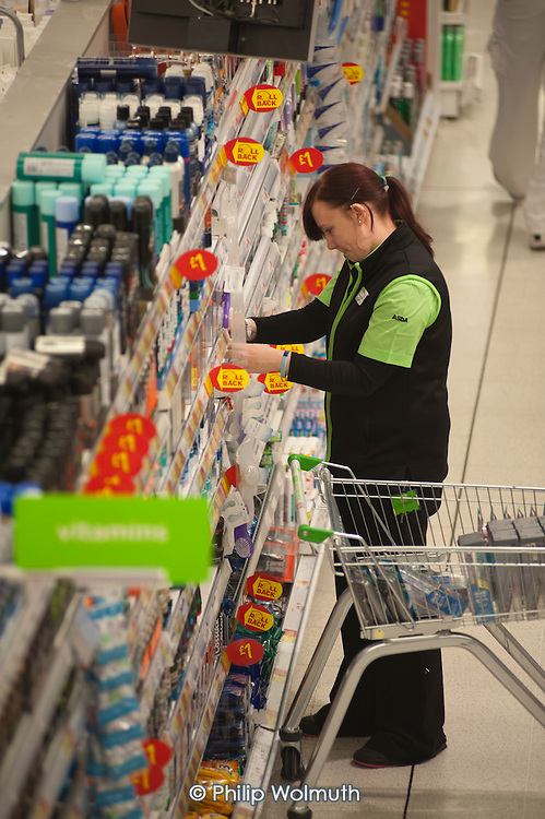 Worker stacking shelves, Asda supermarket, Clapham Junction, London.