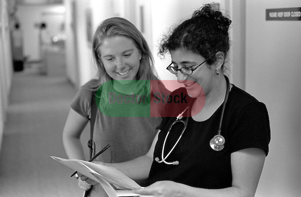 Young female doctor standing in hallway looking over paperwork with young female patient