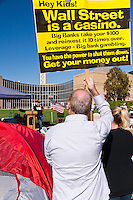 "A protester holds a sign reading ""Hey kids!  Wall Street is a casino …"" while listening to Mark LeVine (of UCI) speak at the Occupy Orange County, Irvine camp on Saturday November 5."