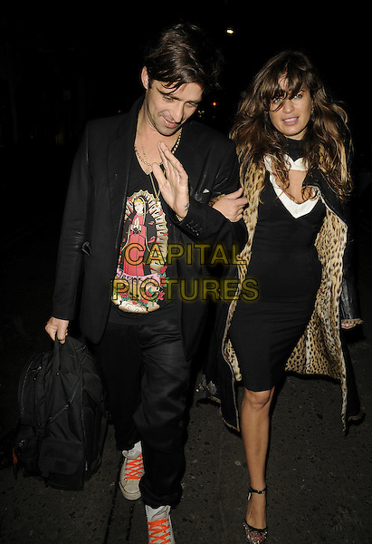 DAN WILLIAMS & JADE JAGGER.The Launch of the new Nokia 5800 phone, Punk nightclub, Soho St., London, England..January 27th, 2009.full length black leather leopard print coat jacket lining skirt top dress trousers arms linked couple backpack jezebel print t-shirt .CAP/CAN.©Can Nguyen/Capital Pictures.