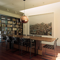 The long polished table in the dining area is surrounded by steel dining chairs covered in leather webbing