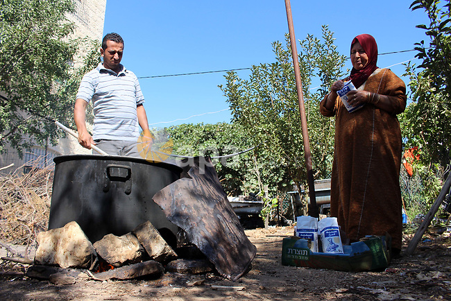 """Palestinians prepare a traditional sweets """"Malban or Turkish delight"""" from grape, the West Bank village of Halhul, near Hebron, on September 29, 2019. Hebron is very famous in grape production as it contains many fields of grapes, the summer is the season of harvesting. Photo by Mosab Shawer"""