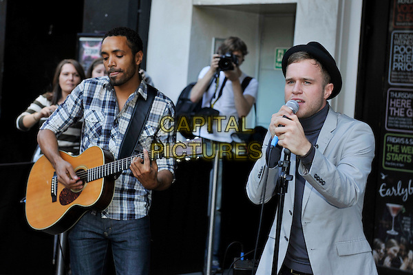 OLLY MURS.Seen busking in Leicester Square, London, England, UK, .October 11th 2010..half length music concert gig performing performance microphone singing black pork pie hat grey gray blazer jacket blue polo neck guitar band .CAP/MAR.© Martin Harris/Capital Pictures.