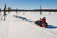 Gerald Sousa sits on his sled and uses ski poles as he runs down a swamp two miles after leaving the the Kaltag checkpoint with the Nulato Hills in the background during the 2010 Iditarod