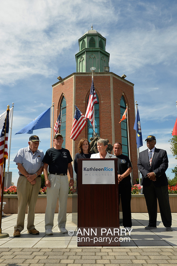 East Meadow, New York, U.S. - September 3, 2014 - Representative CAROLYN MCCARTHY speaks at podium during press conference when KATHLEEN RICE, (in black jacket dress) Democratic congressional candidate (NY-04), releases a whitepaper on veterans policy and announces formation of her campaign's Veterans Advisory Committee, at Veterans Memorial at Eisenhower Park, after touring Northport VA Medical Center with McCarthy. Congresswoman McCarthy and 4 committee members joined Rice for announcement: PAUL ZYDOR, (in blue shirt) of Merrick, U.S. Navy, Korean War Veteran; PAT YNGSTROM, (in black T-shirt and cap) of Merrick, U.S. Army Paratrooper, Vietnam War Veteran; STEVE BONOM, (in black T-shirt and pants) of Massapequa, U.S. Navy, Vietnam War Veteran; and JEREMIAH E. BRYANT, (wearing American Flag tie and black suit) of Rockville Centre, U.S. Army, Vietnam War Veteran. Rice is in her third term as Nassau County District Attorney, Long Island.