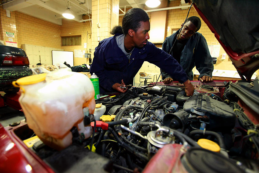 Automotive HS, Brooklyn, NY on Friday, January 22, 2010.  High school students have the opportunity to participate in a special program where they perform basic maintenance and repairs on privately owned cars at very competitive prices.  Students Dwayne Cadet, 18, left, and Harry Cange, 17, perform a tune-up on a car.