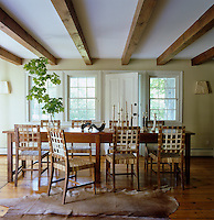An antique dressmaker's table from Argentina, woven hide chairs and a cowhide rug furnish the dining room