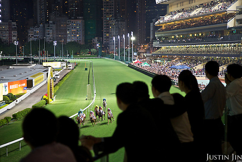 Spectators watch a race at the Hong Kong Jockey Club's Happy Valley racecourse.