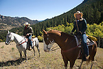 Couple outdoors horseback riding on a crisp and cool fall morning amid aspen groves high in the Rocky Mountains, near Estes Park, Colorado, USA