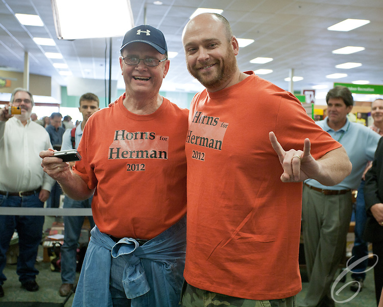 "Two ""Horns for Herman"" pose for pictures as they show off for Presidential candidate Herman Cain in College Station, Texas.  Cain was in town to sign his book ""This is Herman Cain"" on October 6, 2011. College Station is the home of Texas A&M University and the alma mater Cain's Republican rival Rick Perry."