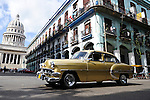 HAVANA - JANUARY 3: A vintage car drives past the Cuban National Capitol Building in Havana, Cuba.  Legislation passed in 2011 has legalized car sales to all Cuban citizens who were previously restricted to owning pre-revolution vehicles.