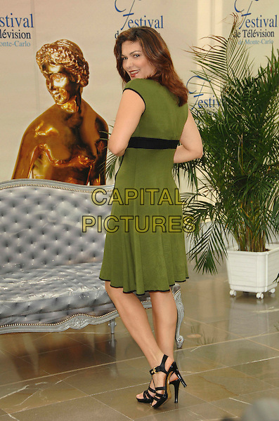 "LAURA HARRING.Photocall promoting the television series ""The Shield"" during the fourth day of the 2008 Monte Carlo Television Festival held at Grimaldi Forum, Monaco, Principality of Monaco,.June 11th, 2008..full length green dress looking back over shoulder black strappy shoes sandals.CAP/TTL .©TTL/Capital Pictures"