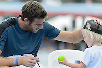MELBOURNE, AUSTRALIA - JANUARY 12: JUAN MARTIN DEL POTRO (ARG) autographs a ball for Lleyton Hewitt's son Cruz after the 2013 AAMI Classic event at the Kooyong Lawn Tennis Club in Melbourne, Australia. Hewitt won  6-1 6-4 (Photo Sydney Low)