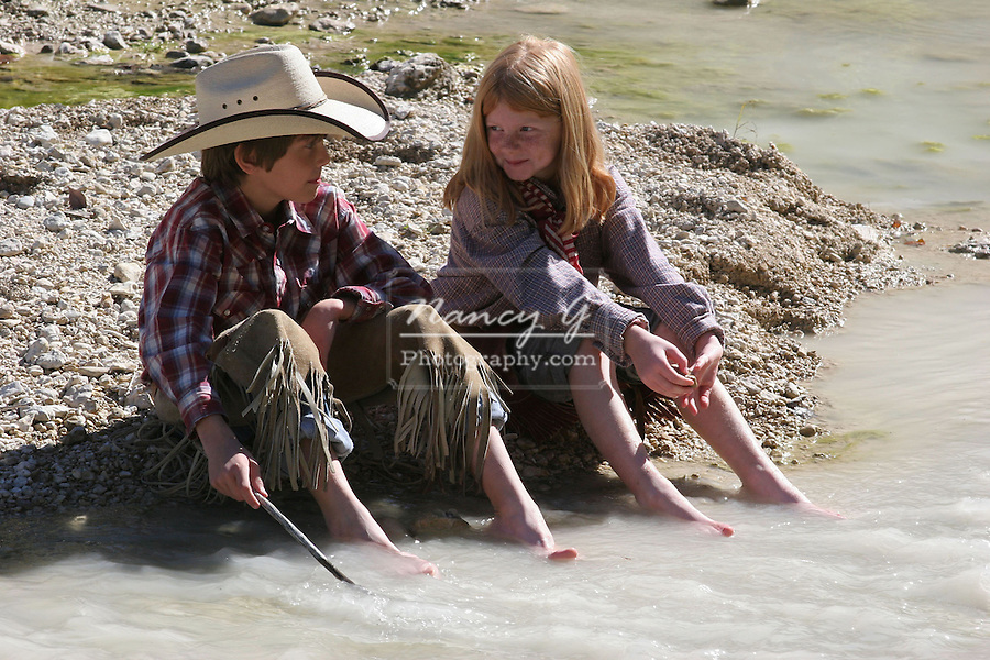 A young cowboy and girl sharing time with their feet in a stream