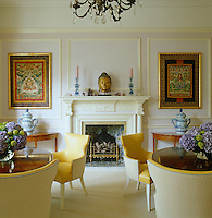 A pair of pedestal tables in the lavender-lacquered dining room either side of a central fireplace flanked by 18th century Indian tankas