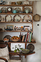 A collection of crockery, ceramics, books and family photographs is displayed on a simple wooden shelving unit in the kitchen