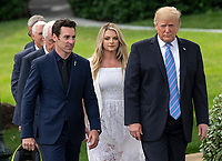 United States President Donald J. Trump, right, walks with winning driver Simon Pagenaud, left, as he greets the 103rd Indianapolis 500 Champions: Team Penske, on the South Lawn of the White House in Washington, DC on Monday, June 10, 2019.  The President took some questions on trade, Mexico, and tariffs against China.  At center is Pagenaud's fiancé Hailey McDermott.<br /> CAP/MPI/RS<br /> ©RS/MPI/Capital Pictures