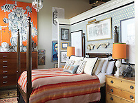 "A partition creates a bedroom and the warm orange tones of a large abstract painting, ""Bettys Revenge"" by Laurel Sparks, are echoed in the bedding and table lamps"
