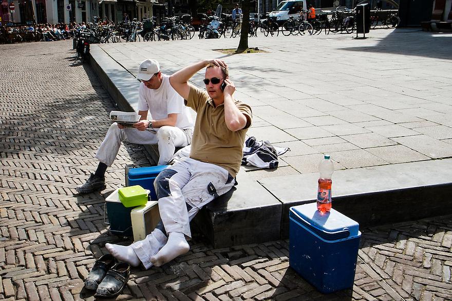 Nederland, Utrecht, 8 april 2014<br /> Pauze. Bouwvakkers, schilders, houden pauze en eten hun lunch, zittend op een randje van het plein bij het Utrechtse stadhuis.<br /> Foto (c) Michiel Wijnbergh
