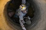MADAGASCAR, region Manajary, town Vohilava, small scale gold mining / MADAGASKAR Mananjary, Vohilava, kleingewerblicher Goldabbau, Goldsucher wie MARIO mit Stirnlampe foerdern Steine uind Sand aus einem Stollen, die am Fluss nach Gold gewaschen werden