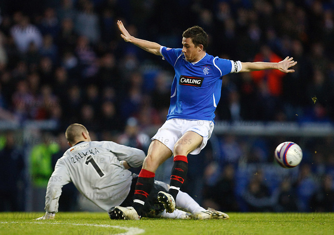 Barry Ferguson knocks the ball away from keper Lukasz Zaluska and it falls to Kyle Lafferty for Rangers second goal