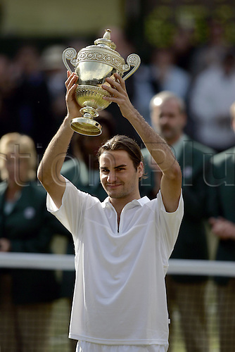 4 July 2004: Swiss defending champion ROGER FEDERER (SUI) holds the trophy above his head in celebration after winning his second men's singles title with victory over Roddick in the Final at the All England Lawn Tennis Championships, Wimbledon, London. Federer beat Roddick 4-6, 7-5, 7-6, 6-4 Photo: Glyn Kirk/Action Plus...040704 Tennis man joy celebrate celebrates celebrations winner winners trophies cup cups