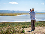 A man uses his cell photo to photograph Soda Lake and the Temblor Range during the spring wildflower bloom from the overlook, Carrizo Plain, San Luis Obispo County, Calif.