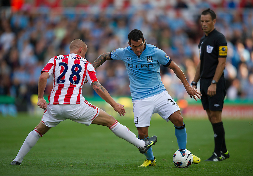 Referee Mark Clattenburg watches as Manchester City's Carlos Tevez dribbles past Stoke City's Andy Wilkinson ..Football - Barclays Premiership - Stoke City v Manchester City - Saturday 15th September 2012 - Britannia Stadium - Stoke..