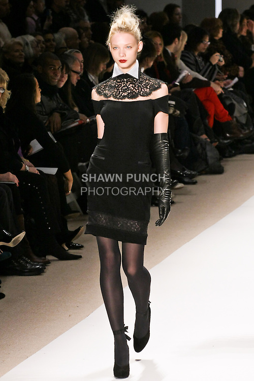 Daria Werbowy walks the runway in a black off shoulder short sleeve cocktail dress with lace collar and hemline details, by Georges Chakra for the Edition Autumn Winter 2010-2011 collection, during Mercedes-Benz Fashion Week Fall 2010.