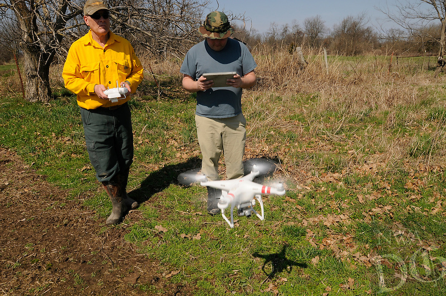 NWA Democrat-Gazette/ J.T. WAMPLER -- Bruce Shackleford, left, and Neil Bilbe launch an aerial drone to monitor the controlled burn at the Woolsey Wet Prairie Sanctuary Monday March 23, 2015.