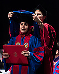 The College of Law students are hooded by associate deans Allison Tirres and Margit Livingston. The bestowal of the hood on the graduate symbolizes the awarding of their degree at the DePaul University College of Law commencement ceremony, Sunday, May 14, 2017, at the Rosemont Theatre in Rosemont, IL, where some 240 students received their Juris Doctors or Master of Laws degrees. (DePaul University/Jeff Carrion)