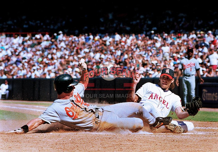 Brady Anderson of the Baltimore Orioles beats the tag by Mike James of the California Angels during a 1995 season game at Anaheim Stadium in Anaheim,California.(Larry Goren/Four Seam Images)