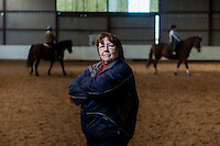 FAO Laura Lean.<br /> Friday 20 January 2017<br /> Pictured: Sue Scourfield looks on as the horses canter around the barn <br /> Re: Sue Scourfield's riding school is  being hit by increasing business rates.