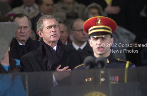 United States President George W. Bush holds his hand over his heart as his dad, former U.S. President George H.W. Bush looks on during the inauguration ceremony at the U.S. Capitol in Washington, D.C. on January 20, 2001..Credit: David N. Berkowitz for Newsweek - Pool via CNP.